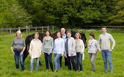 Das Team posiert mit einem Pferd auf der Weide