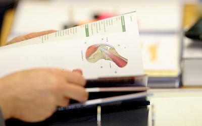 Ein Teilnehmer hat ein Anatomiebuch aufgeschlagen in seinen Händen