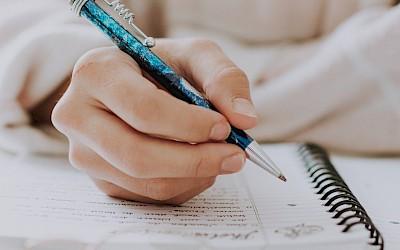 Jemand macht sich Notizen in ein Notizbuch