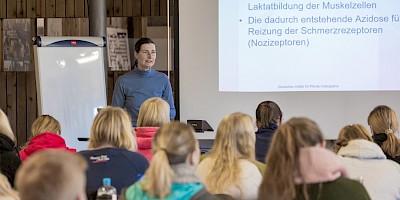 Teilnehmer hören der Dozentin im theoretischen Unterricht im Klassenraum zu