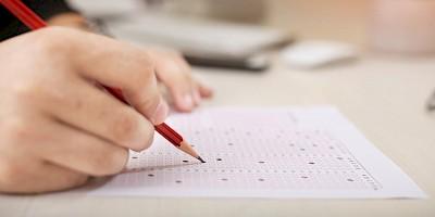 Ein Prüfling füllt ein Prüfungsbogen aus
