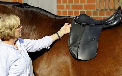 Beatrix Schulte Wien zeigt einen Sattel auf dem Pferderücken